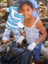 Children participate in a beach clean up.  It took them only minutes to fill large trash bags with garbage found along their community's beach.